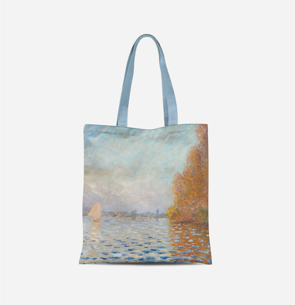 A bag with long light blue handles covered in an impressionist painting of a light blue sky reflecting in a lake, with a large autumnal tree to the right and a small white sail boat to the left.
