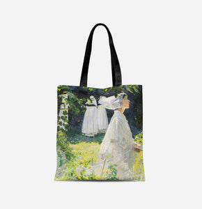 A bag with long black handles covered in a painting of a woman in white walking towards the right, with white lilies in the foreground and greenery behind her.