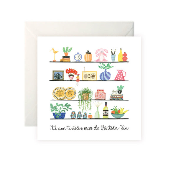 A white card with a drawing of shelves. The shelves have different colourful knick knacks including potted plants, vases, dishes, toys and books. 'Níl aon Tinteán mar do Thinteán Féin' is written at the bottom in black cursive.