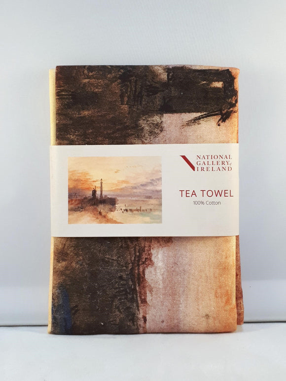 A folded tea towel with a grey label around the centre. The label shows a vibrant watercolour of a beachside scene at sunset. A lighthouse and windmill are silhouetted in black against an orange and purple sky.