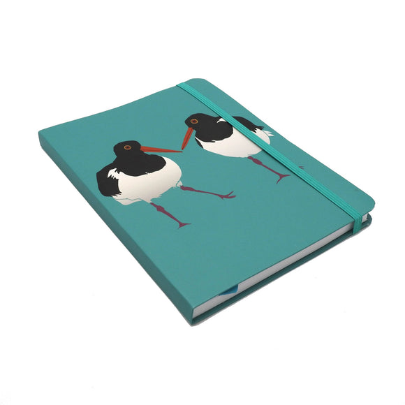 A notebook with an illustration of two black and white oystercatcher birds on a teal cover. It is held closed by a matching teal elastic band.