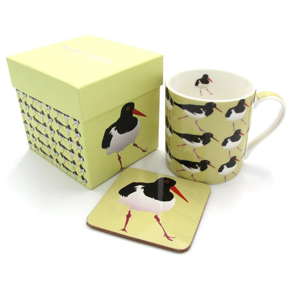 A yellow box, mug and coaster. The mug has an illustration of an oystercatcher as a repeated pattern The coaster has a single bird. The box has a single bird on one side, the repeated pattern on the other, and Annabel Langrish in silver on the lid.