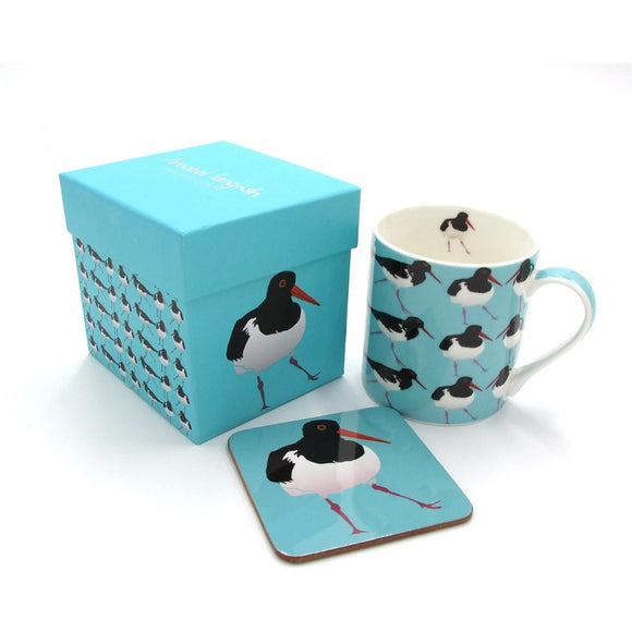 A light blue box, mug and coaster. The mug has an illustration of an oystercatcher as a repeated pattern The coaster has a single bird. The box has a single bird on one side, the repeated pattern on the other, and Annabel Langrish in silver on the lid.