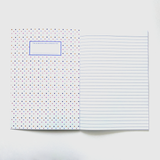 A notebook open to the first page. The writing page is lined. The inside cover is a pattern of small polka dots in different colours. There is a space to write a name.