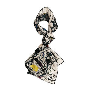 A rectangular scarf knotted in a loop covered in a design of black paint splatter with splashes of yellow, red and blue.