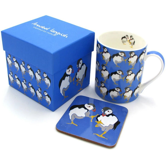 A vivid blue box, mug and coaster. The mug has an illustration of two puffins as a repeated pattern The coaster has the two birds. The box has two puffins on one side, the repeated pattern on the other, and Annabel Langrish in silver on the lid.