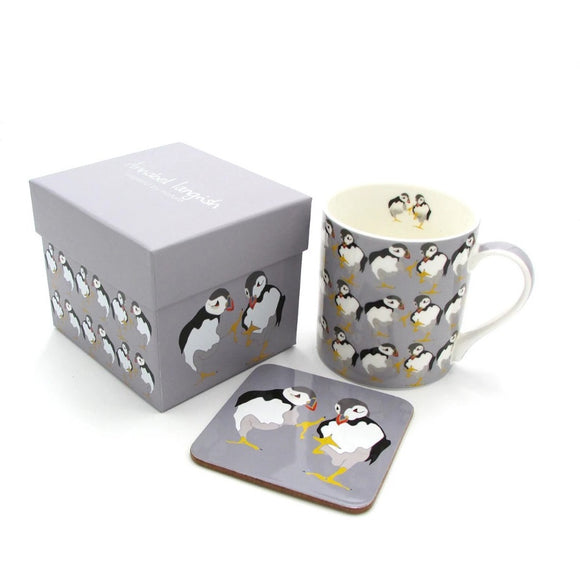 A grey box, mug and coaster. The mug has an illustration of two puffins as a repeated pattern The coaster has the two birds. The box has two puffins on one side, the repeated pattern on the other, and Annabel Langrish in silver on the lid.