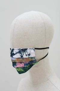 A pleated face mask on a mannequin head. The design is of an impressionist style landscape at the edge of a forest in shades of green, pink, brown and an almost white sky. It has black ear straos.