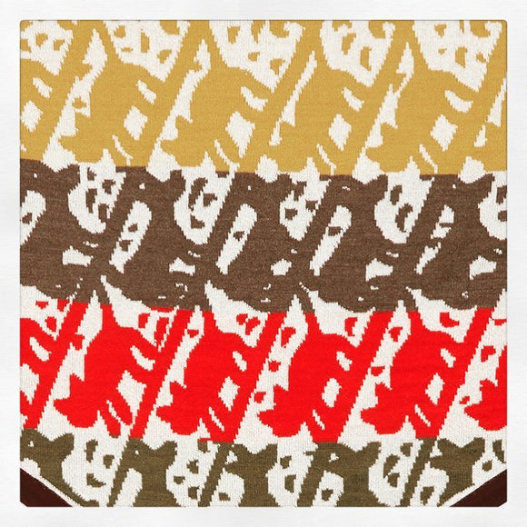 Detail image from knitted triangle scarf. The design features diagonal cream stripes with the shapes of cats and dogs in the negative space. These are coloured by bold horizontal stripes of mustard, brown, coral and green running across the scarf.