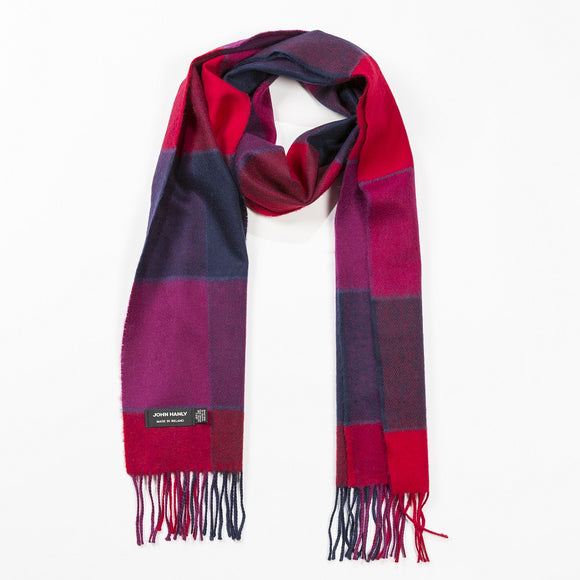 A scarf with a thick block check in shades of red, purple, dark pink and navy, with a matching fringe on both ends.