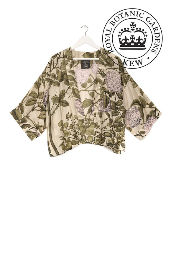 A short, boxy beige kimono covered in drawings of light pink flowers and dark green leaves and thorned stems. Thick lines of stitches form the collar and opening edge trim.