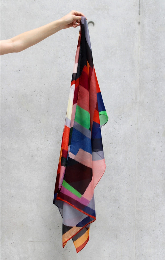 A colourful scarf draped from a hand. Its is covered in shapes in different colours including orange, red, green, blue and yellow.