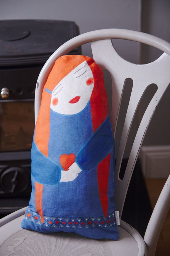 A roughly oval shaped flat cushion with a squared off bottom. It is printed with a simple, stylised design of a woman with long red hair wearing a blue dress with a pattern of small hearts along the bottom. She holds a small red heart.