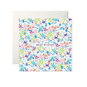 A white card with a drawn pattern of flowers and butterflies in bright colours. In the centre 'Best Wishes' is written in black capitals.