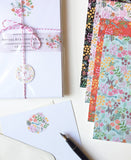 The set opened out showing a cream envelope and colourful designs on the writing paper.