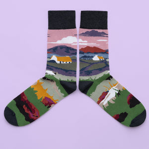 A pair of socks of a rural landscape with thatched cottages and a sheep. Mountains, water and a pink sky are in the background. The foot is more fields and a sheep, with a wine toe, heel and cuff.