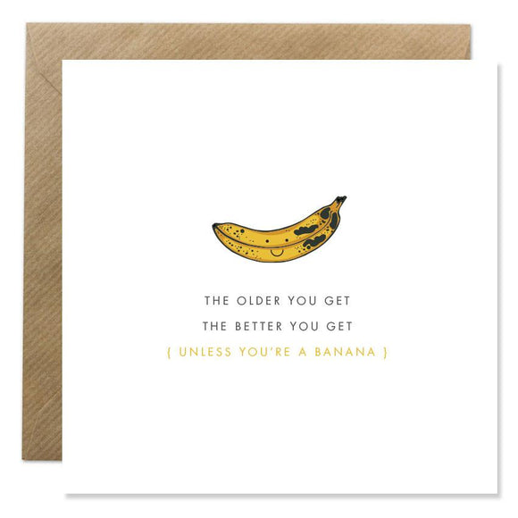 A white card with a simple illustration of a smiling, browning banana. Below 'The older you get the better you get' is in thin capital letters with '(unless you're a banana)' underneath in yellow letters.