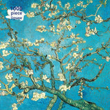 The cover of this box has a detailed painting depicting the top branches of an almond tree in blossom. The branches of the tree have a textured bark-like quality and they are in tones of green and curve in many directions. The blossoms on the branches are cream-coloured. The background is a light blue. The top left hand corner has text that reads 1000 piece jigsaw.