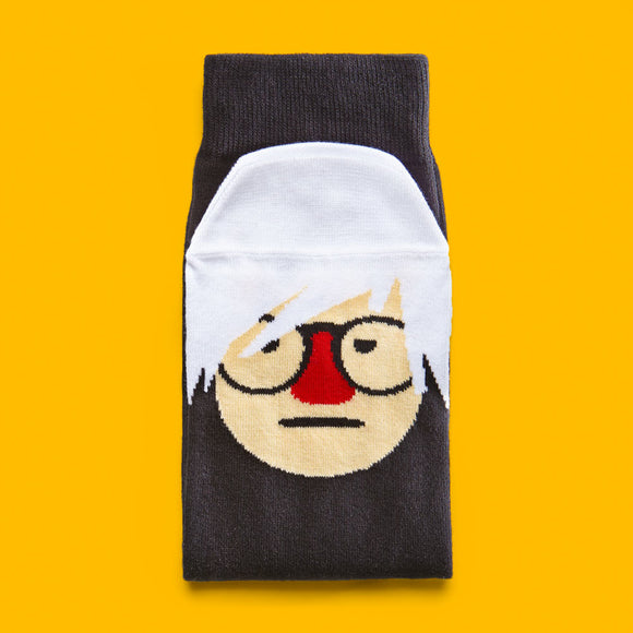 A folded black sock with a cartoon illustration of a man in glasses with white hair on the toe and lower foot part.