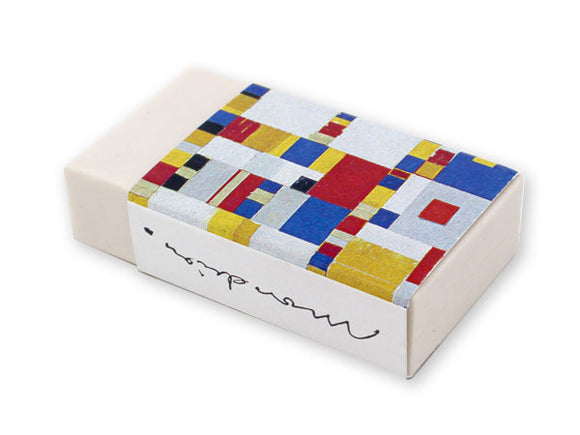 A white eraser in a card sleeve. The sleeve is covered in small of red, yellow, grey, white, black and blue squares in different sizes and patterns. A reproduction of Mondrian's signature is on the side.