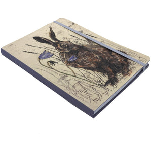 A notebook with an illustration of a dark brown hare sitting in outlined grass with two tall purple flowers on the cover. It is held closed by a lilac elastic matching the notebook's spine.