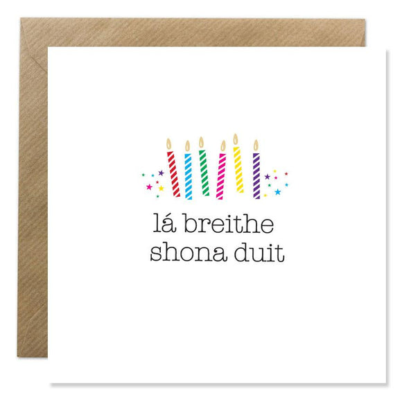 A white card with a simple, brightly coloured illustration of six candles, with stars on either side. 'Lá breithe shona duit' is written below in thin, black lower case letters.