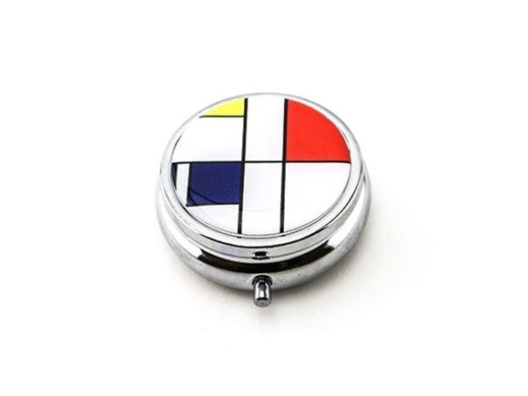 A round silver box with an image of white, red, blue and yellow rectangles separated by black lines on top.