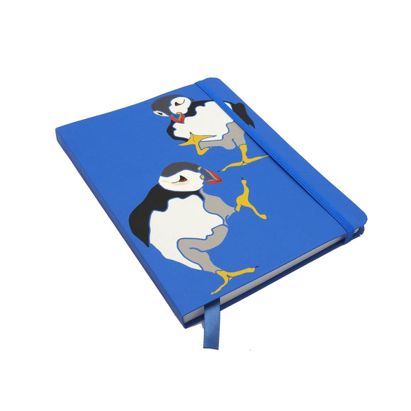 A notebook with an illustration of two puffin birds on a bright blue cover. It is held closed by a matching blue elastic band.