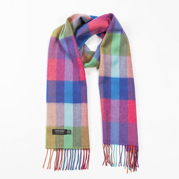A brightly coloured scarf with thick overlapping vertical and horizontal stripes in shades of red, blue, green and pink, with matching fringe across the ends.