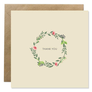 A beige card with a wreath of green leaves and pink flowers in the middle. 'Thank you' is in the centre in small, thin black capital letters.