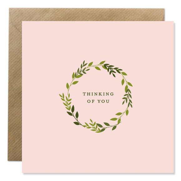 A pink card with a wreath of green leaves in the middle. 'Thinking of you' is in the centre in small, thin black capital letters.