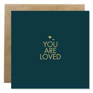 A dark navy card with 'You are loved' in gold capital letters in the centre. Two very small gold hearts are above.