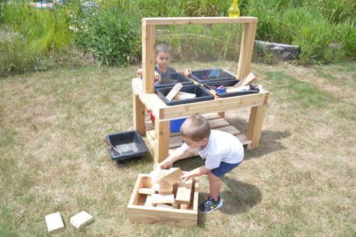 Two young boys on either side of a wooden 4-bin social distancing sensory table. Box of blocks featured but not included.
