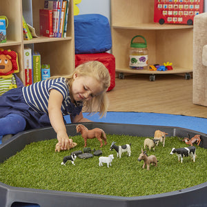 A young girl plays with farm animals on the artificial active world tray turf grass.