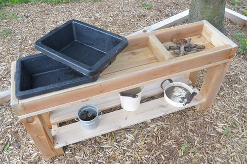Wooden 3-bin sensory table with rubber buckets. The bottom shelf features several metal bins not included with the product.