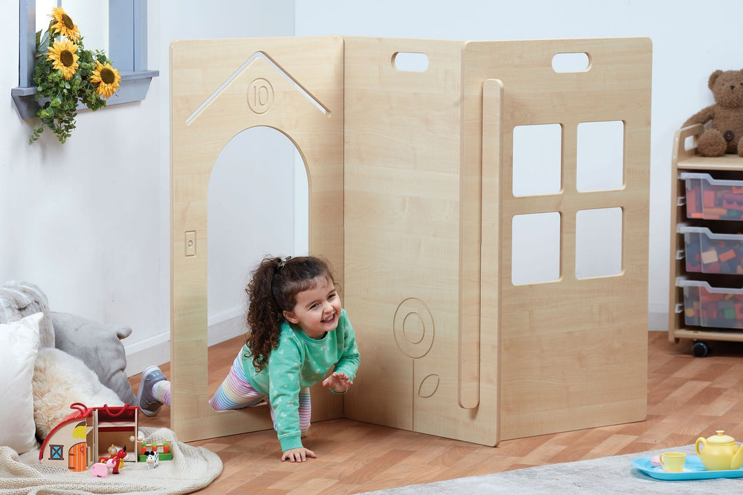 Young girl crawling through the opening in a 3-panel house set.