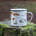 Load image into Gallery viewer, We are in love with our ecology enamelware mugs! Mushrooms of all shapes and sizes adorn this classically illustrated enamel mug. Any forager's best friend! These mugs are a perfect eco-friendly alternative to disposable cups. Available in a range of styles! Bring the magic of the outdoors in, or embrace nature or take it with you!