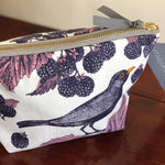 Load image into Gallery viewer, Handprinted with a gorgeous blackbird and bramble design, store all your best bits in this gorgeous cosmetic bag in rich purples and deep inky blues - perfect for your all of your treasures whether for day or night! White cosmetic bag hand printed with purple blackbirds and brambles with pink leaf detail.