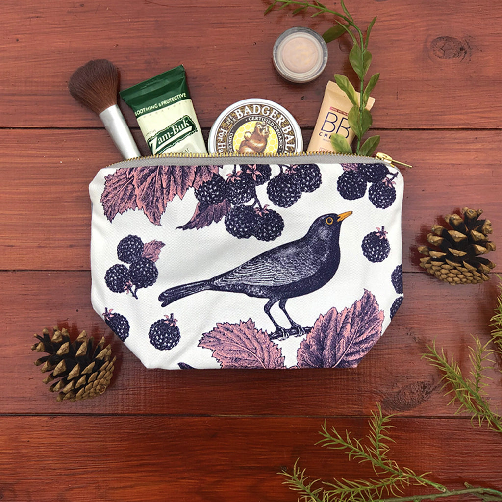 Handprinted with a gorgeous blackbird and bramble design, store all your best bits in this gorgeous cosmetic bag in rich purples and deep inky blues - perfect for your all of your treasures whether for day or night! White cosmetic bag hand printed with purple blackbirds and brambles with pink leaf detail.