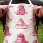 Load image into Gallery viewer, Be the star baker with our gorgeous hand printed 100% cotton aprons! In a mouth watering raspberry pink Jelly & Cake design, this apron conjures up the feeling of kitchens of the past - crafting those perfect creations not just at seasonal celebrations, but all year round! Get practicing in this high quality Thornback & Peel treat!
