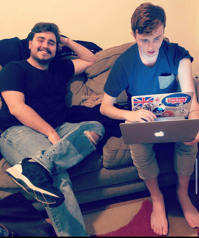 two friends on a couch. One with a Laptop, the other smiling