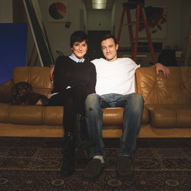 Adam and Jenna Meikle sitting on a couch at Meikle Studios