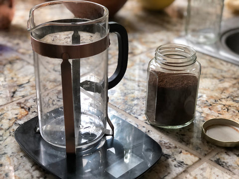 French press on scale with coffee grounds