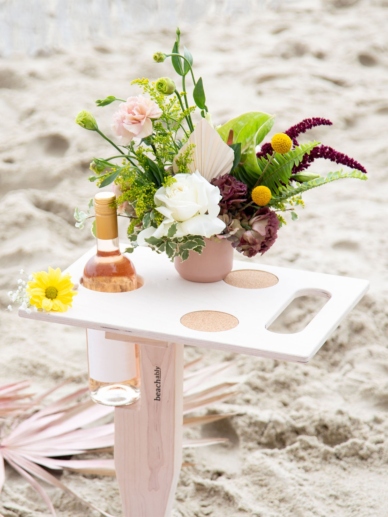 Goulburn portable beach table in beach blonde color unfolded standing up in sand at beach with refreshment drinks and floral decor