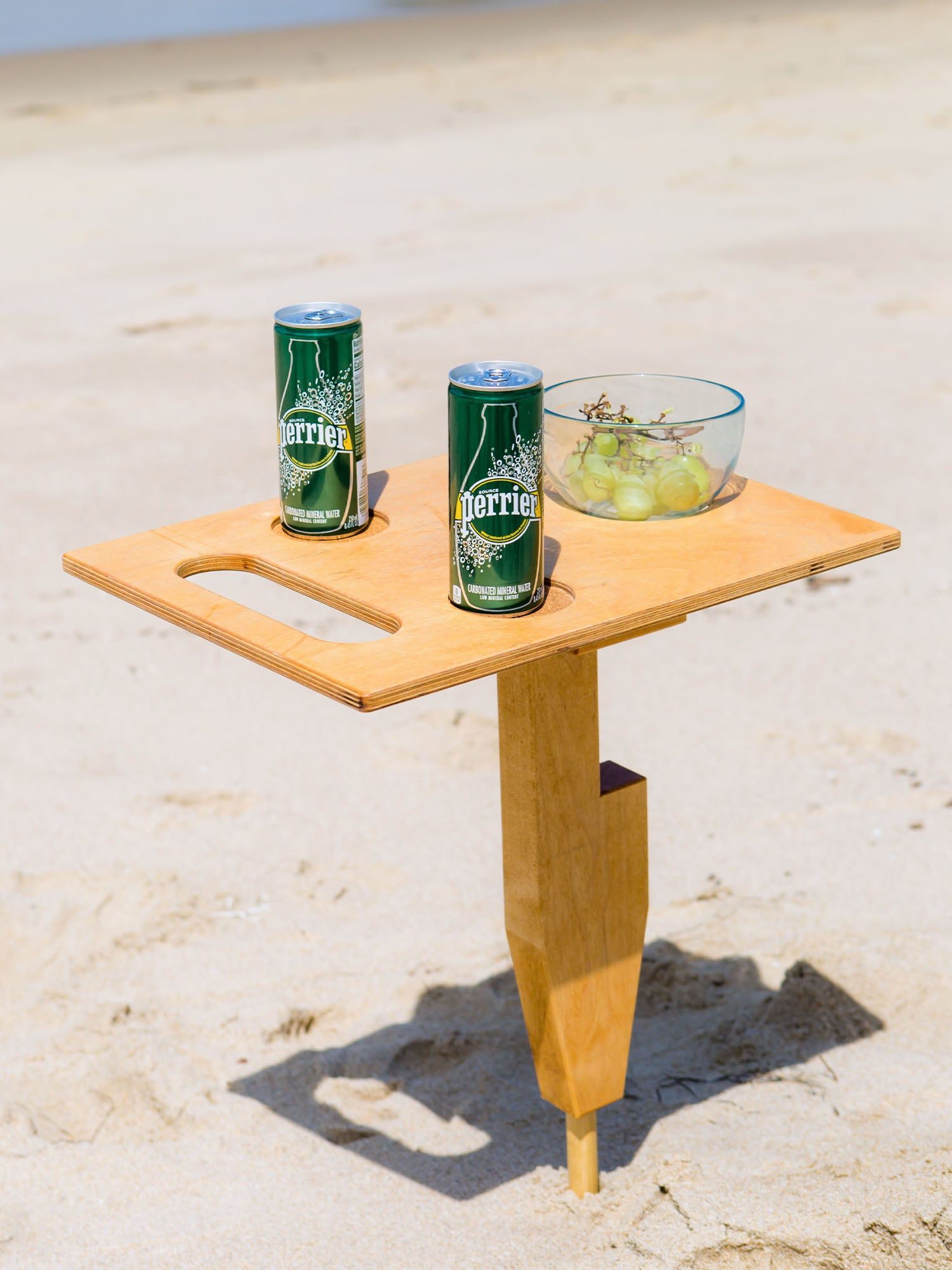 Goulburn portable beach table in naturally sunkissed color unfolded standing up in sand at beach with refreshment drinks and fruit