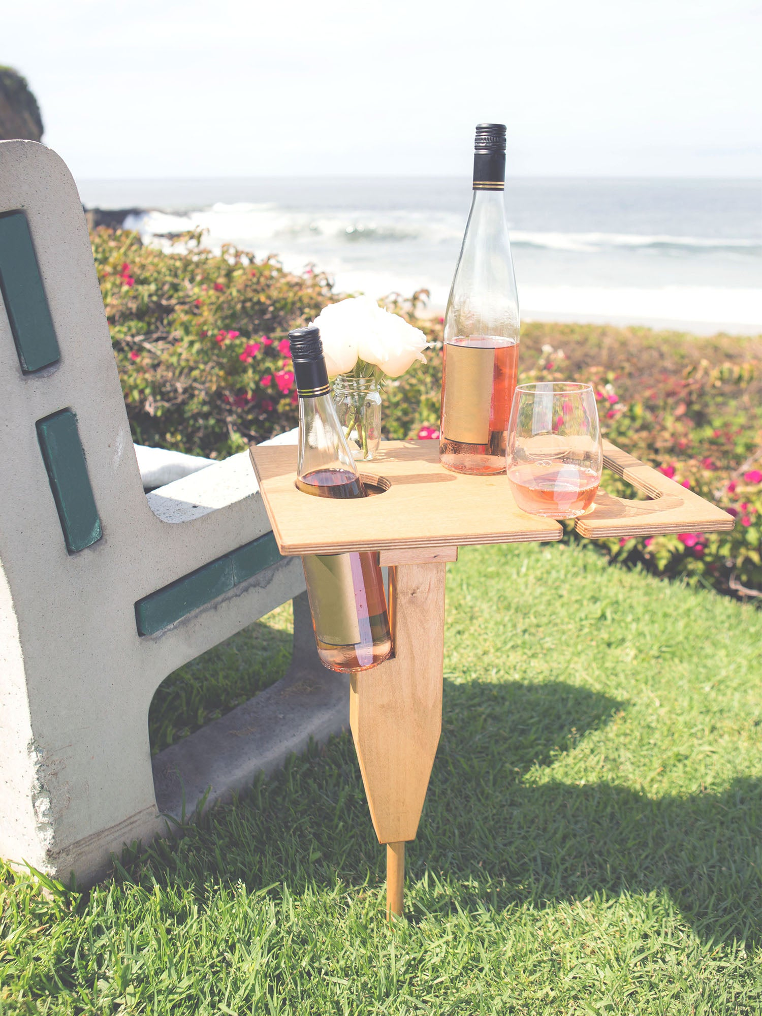 Murray portable beach table in naturally sunkissed color unfolded standing up in grass at park with refreshment drinks