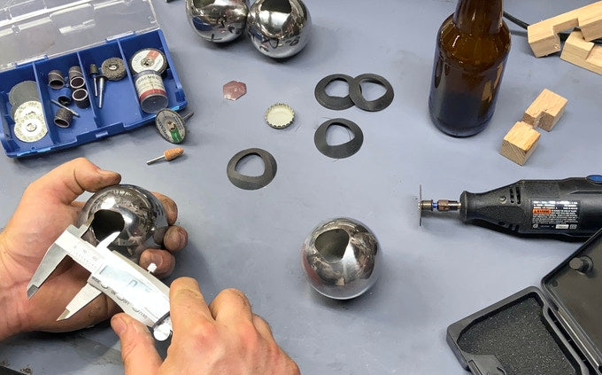Two hands measure a prototype of the Convex bottle opener on a blue counter top surrounded by tools and parts.