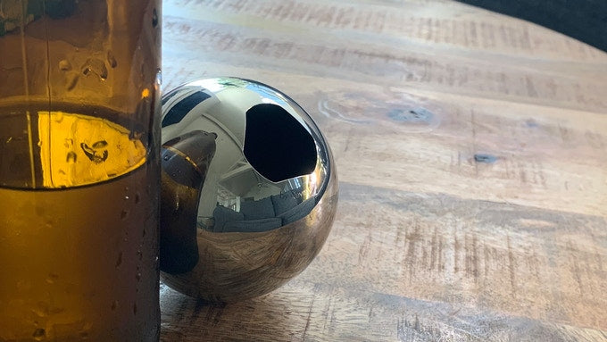 A stainless steel bottle opener hides behind a brown bottle on a wooden coffee table.
