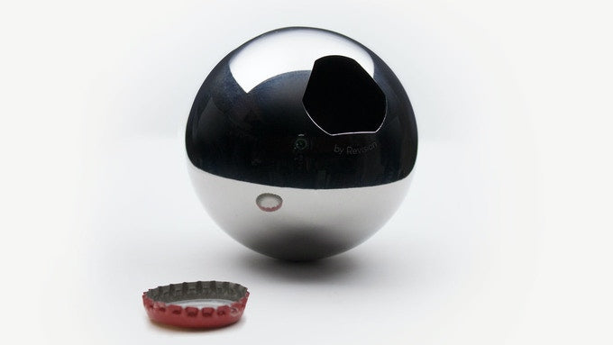 One stainlesss steel Convex bottle opener sits on a white background next a red bottle cap.