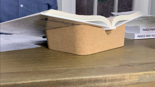 Revision Cork Booklift holds hevy college text book on wooden desk while person sudies in background.